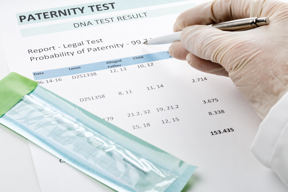 Close up of a gloved hand holding a pen near a paternity test result.